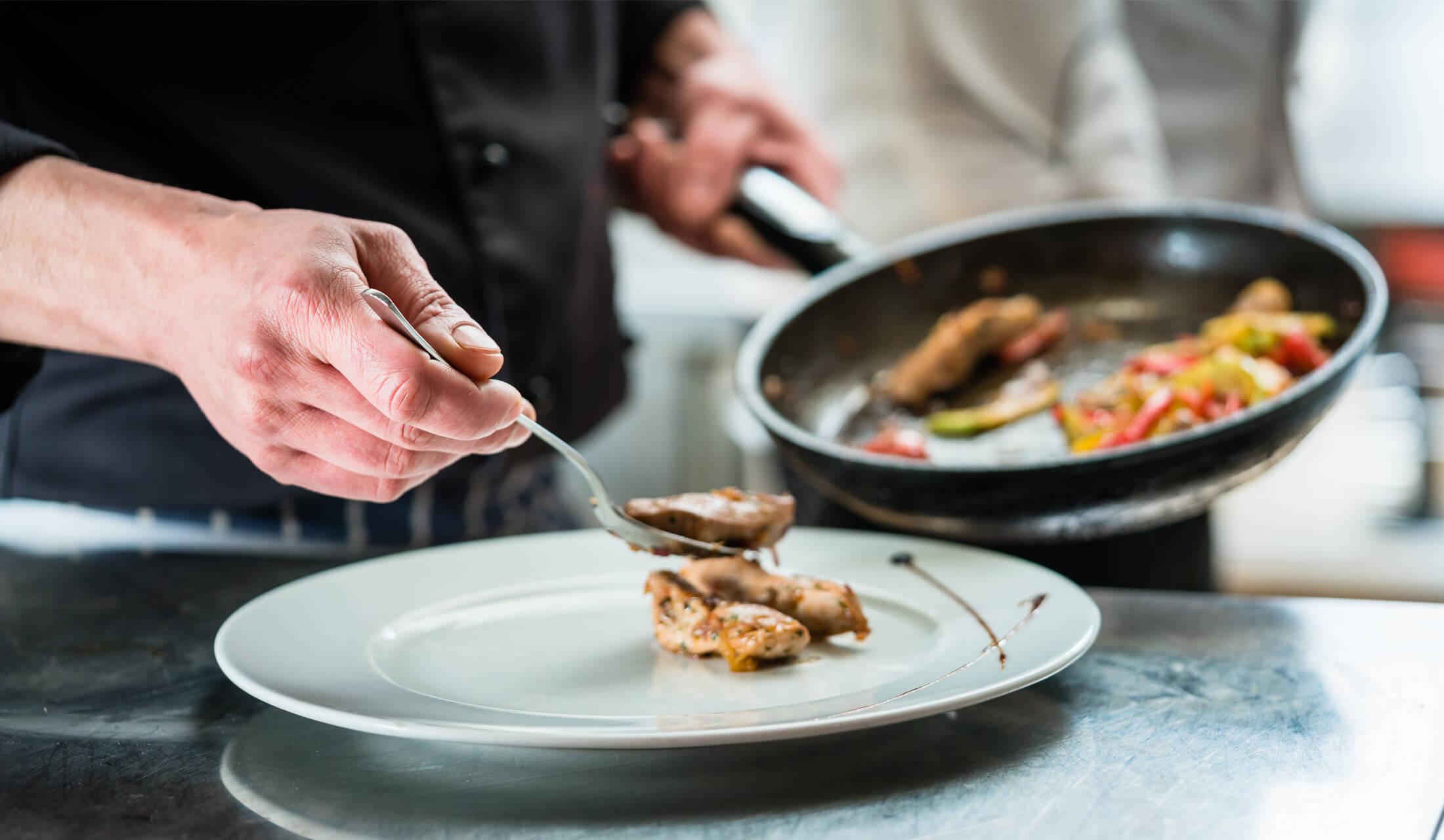 黒いコックコートを着たシェフが調理した肉の料理をフライパンからお皿へ盛り付けている