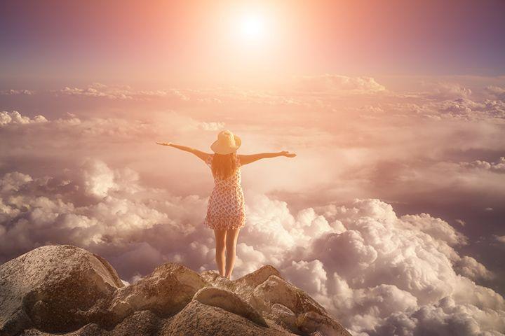 日の出の光を浴びる女性