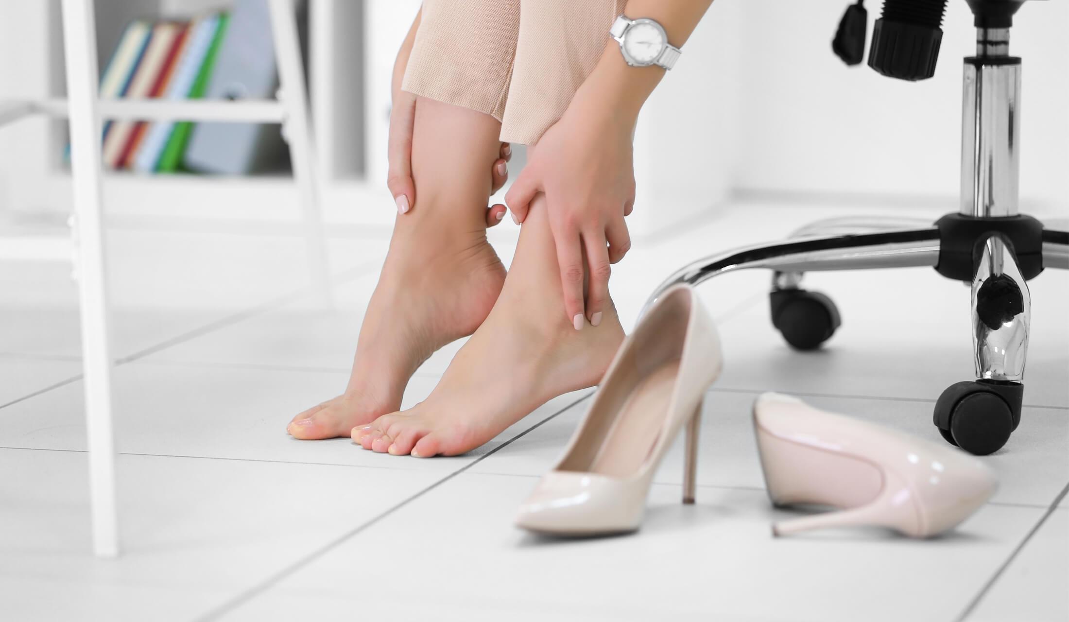 女性がライトベージュのハイヒールを脱ぎ、痛む足首をさすっている様子