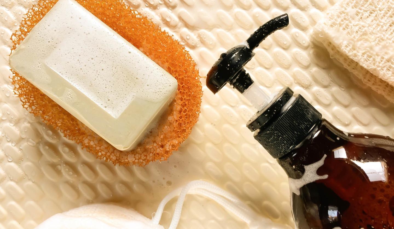 固形石鹸が上にのった掃除用スポンジとポンプ式ボトル