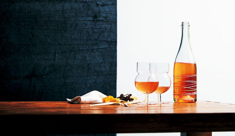 オレンジワインが注がれたワイングラスとオレンジワインのボトル、ドライフルーツが乗ったテーブル