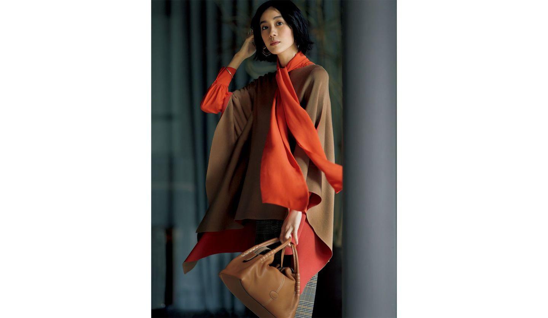 キャメルブラウンのニットポンチョに、鮮やかなオレンジのボウブラウスを合わせたスタイルを纏った女性