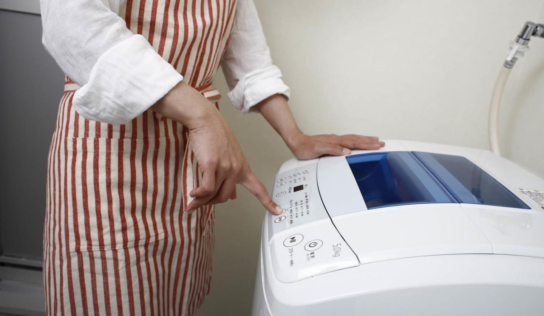 洗濯機のボタンを押している女性