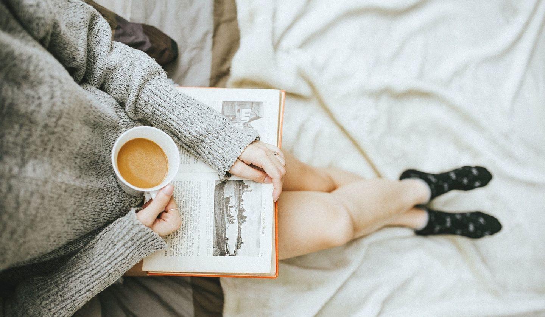 女性が飲み物を片手に読書をしてくつろぐ画像