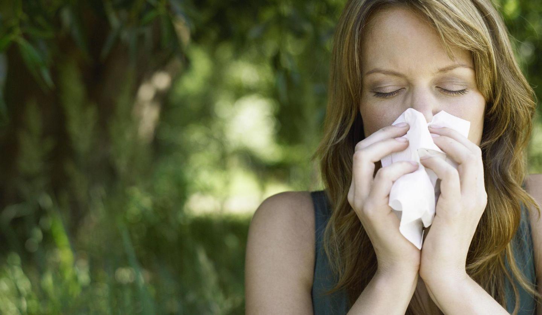 花粉症で鼻をかむ女性のイメージ写真