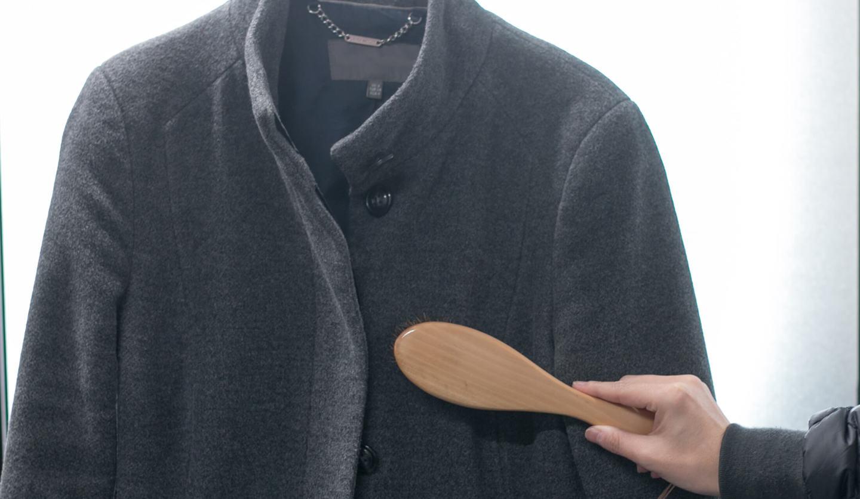 グレーのウールコートにブラシをかけている