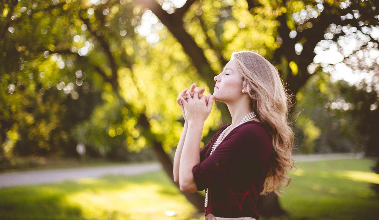 木漏れ日のなかで祈る女性