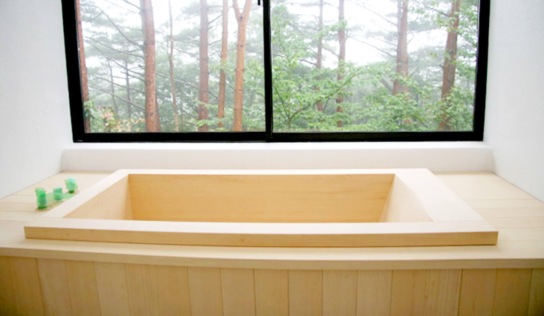 エステック アソシエイツが施工した個人宅に設置された国産のヒノキ風呂。窓の外は、森林が広がっている。