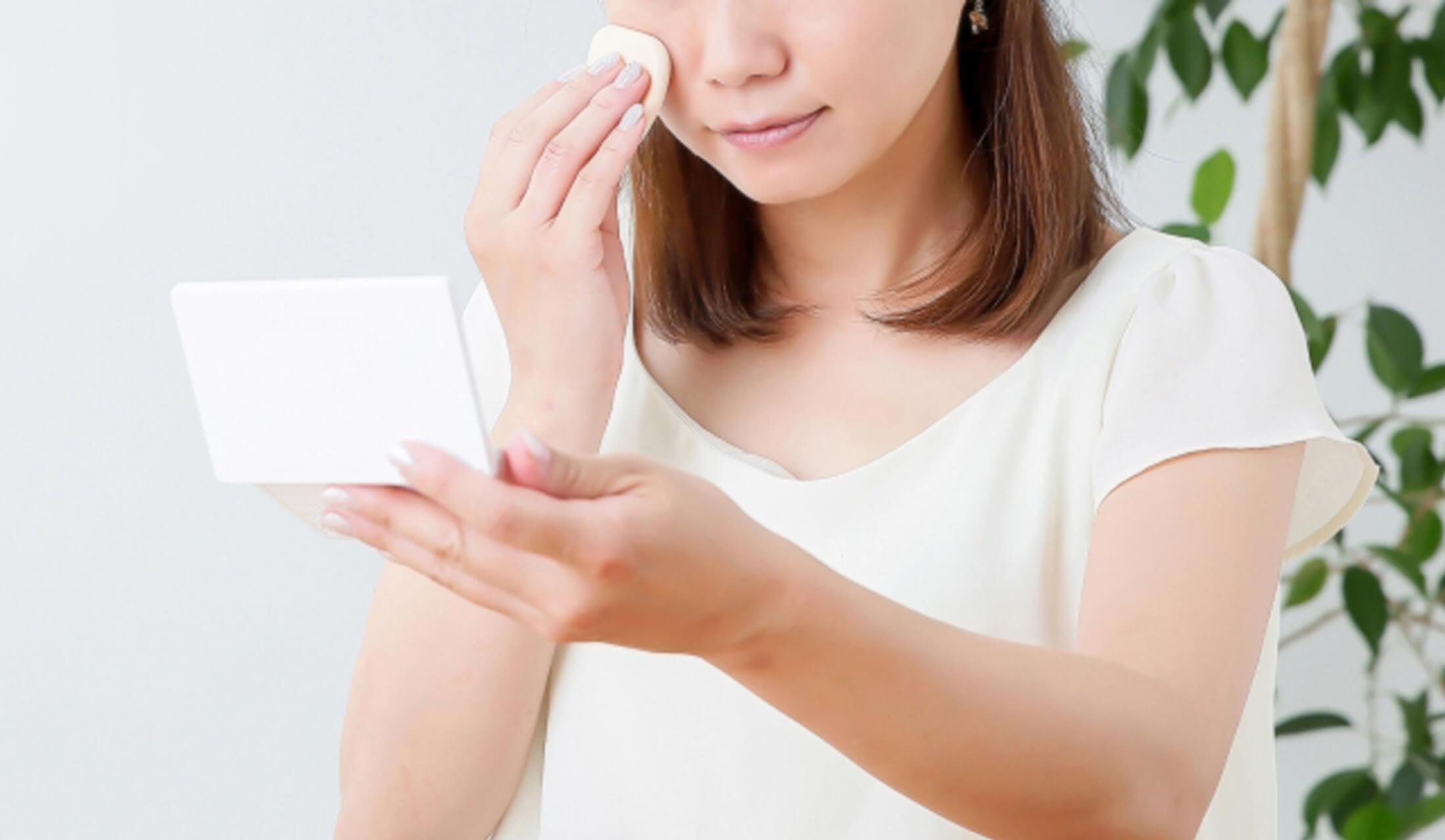女性がコンパクトを左手に持ち、右手でパフを頬に当てながら化粧をしている