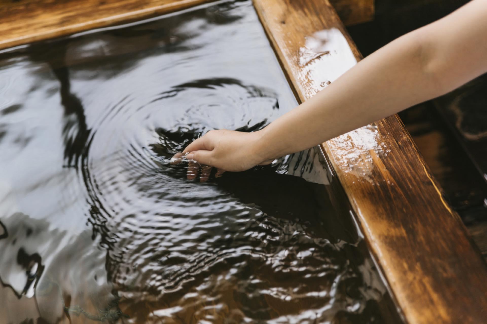 女性が温泉の湯船に手を入れているところ