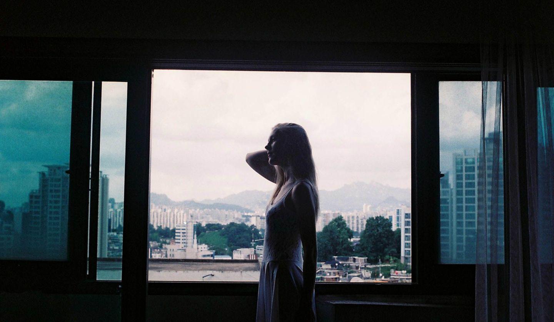 窓の前に立つ女性
