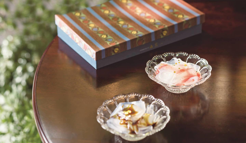 くずきりの盛られたガラスの器が2つ机に乗っており、奥には植物のモチーフがプリントされた箱が置いてある