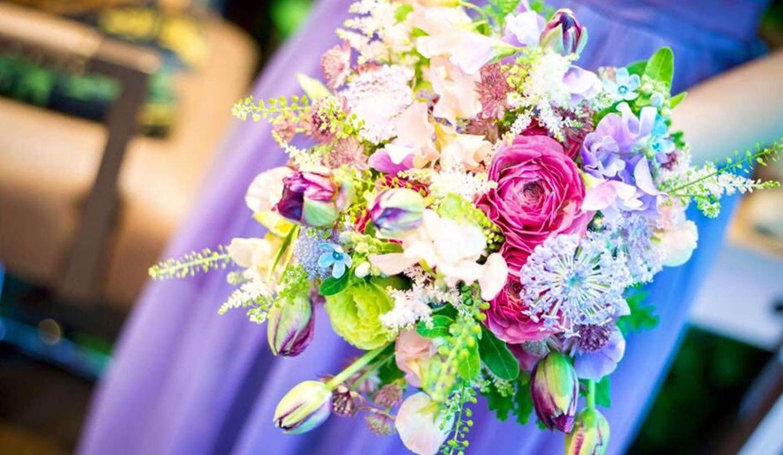 ドレスを着た女性がもつ花束の写真