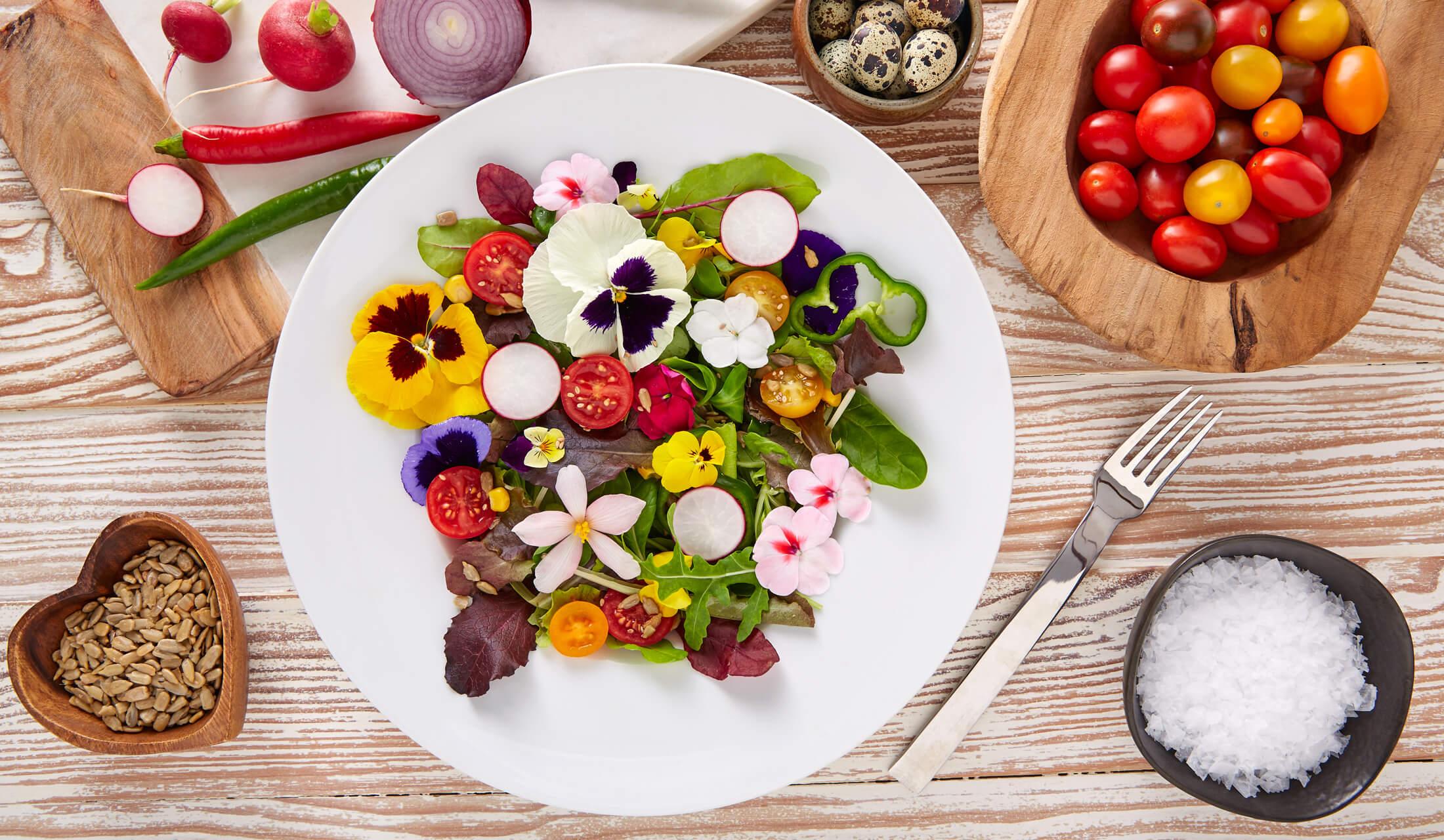 白いお皿の上に、パンジーなどの食べられるお花と赤と黄色のトマトで飾られた生野菜サラダがあり、そのお皿の周囲にフォークや塩、トマトなどが置かれている