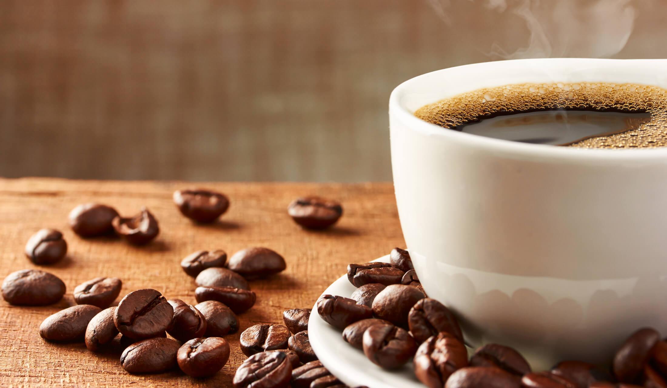 白いソーサー付のマグカップに湯気がたつコーヒーが入れられ、その周りにコーヒー豆が散らばっている