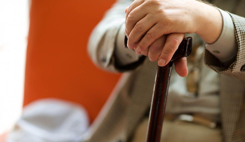 杖に手を置き、椅子に座る男性の手元