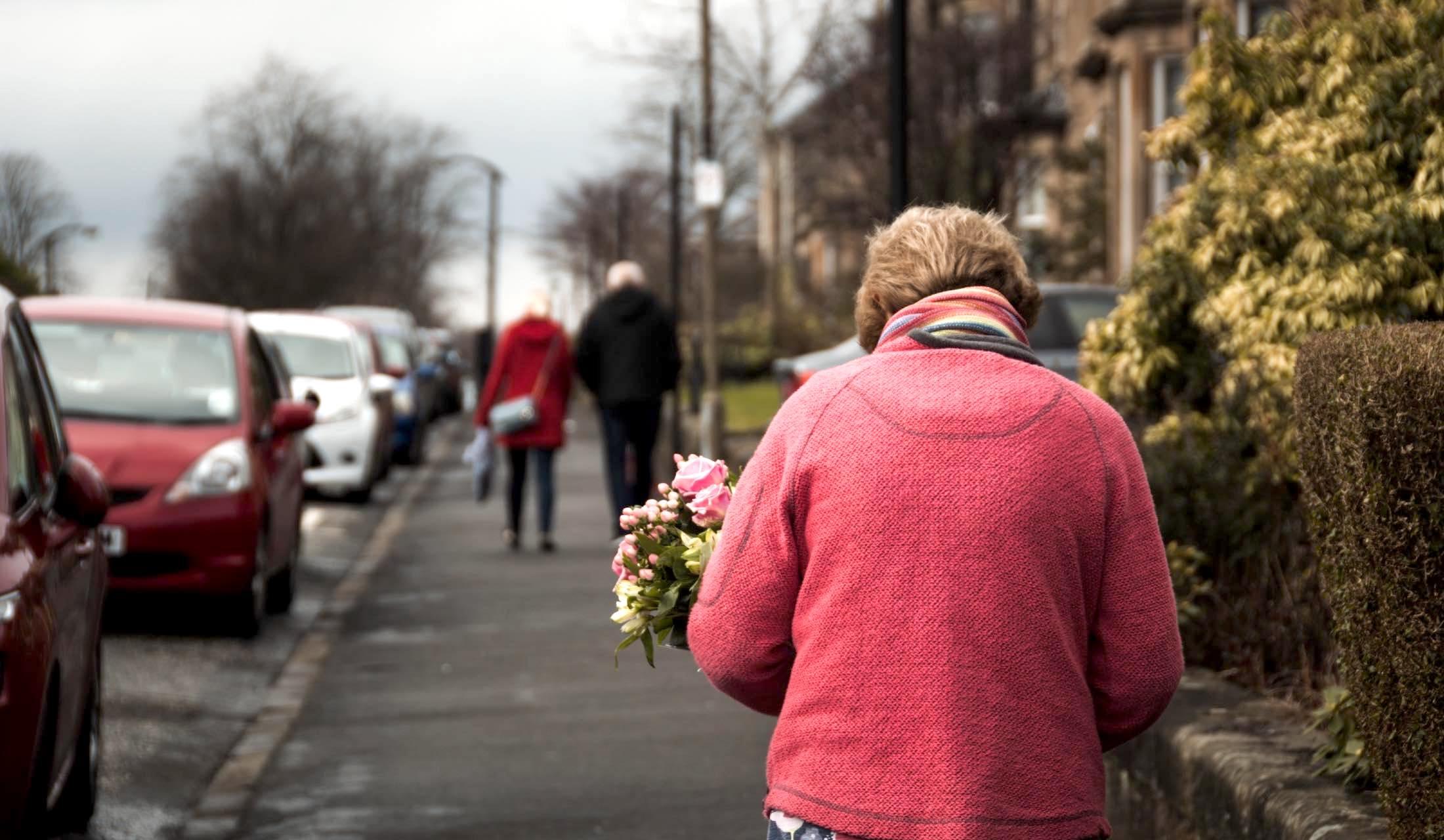 花束を抱える老婆