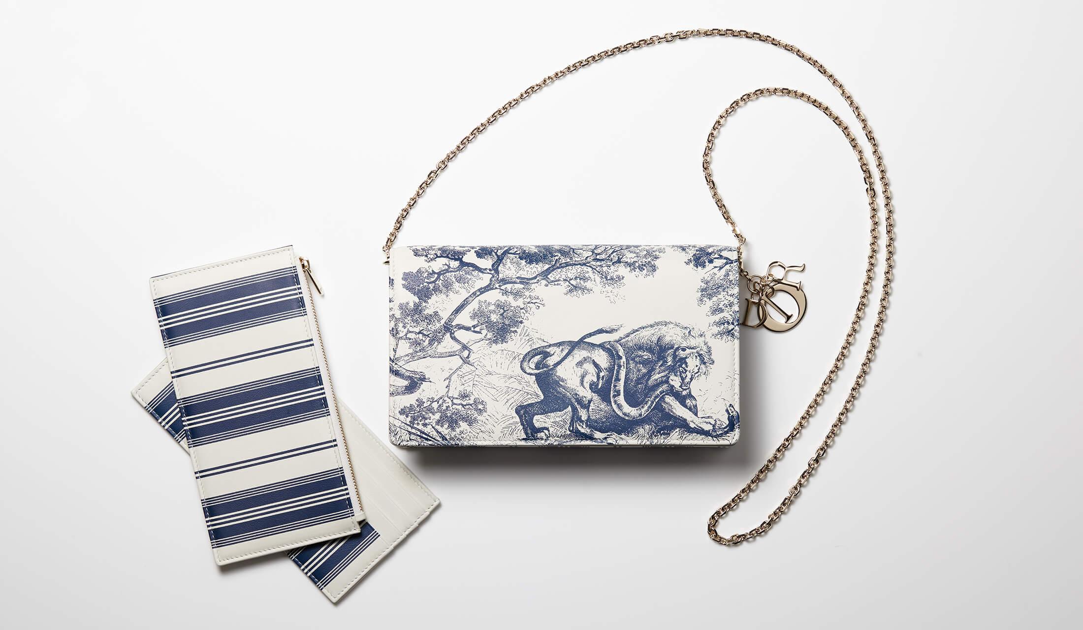 白ベースにブルーで動物や植物、ストライプ柄が描かれたウォレットとカードホルダーのセット