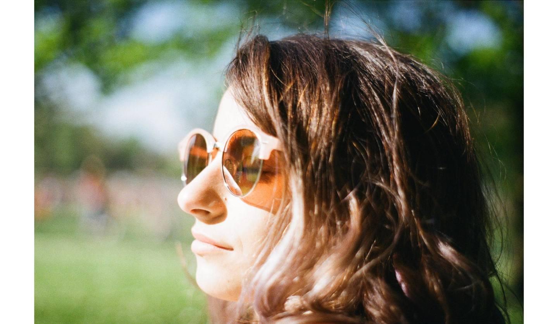 サングラスをかけて日差しを浴びる女性