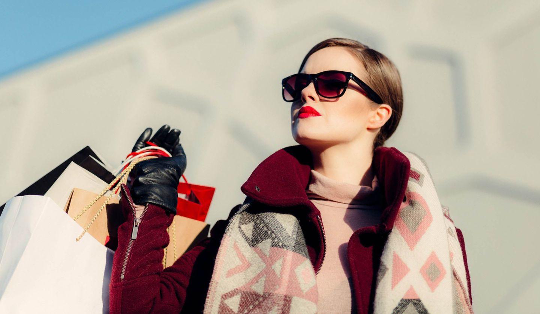 たくさんのショッパーを担いで空を見上げている女性