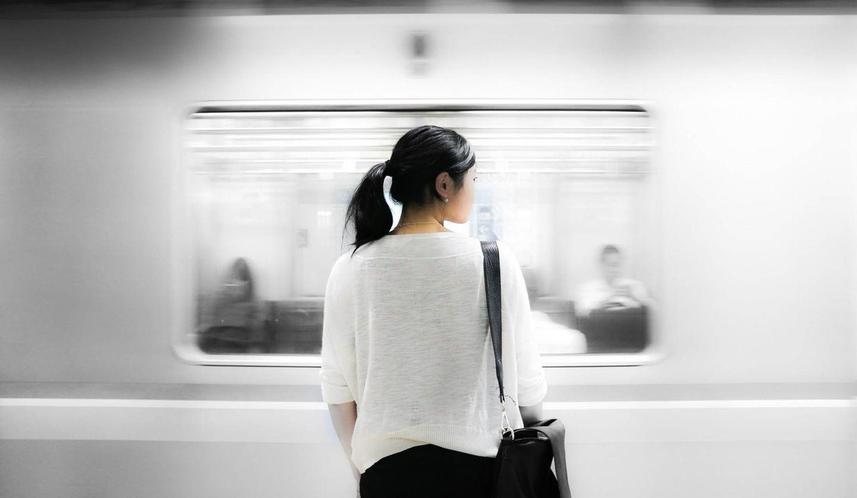 ホームで電車が過ぎるのを待つ女性