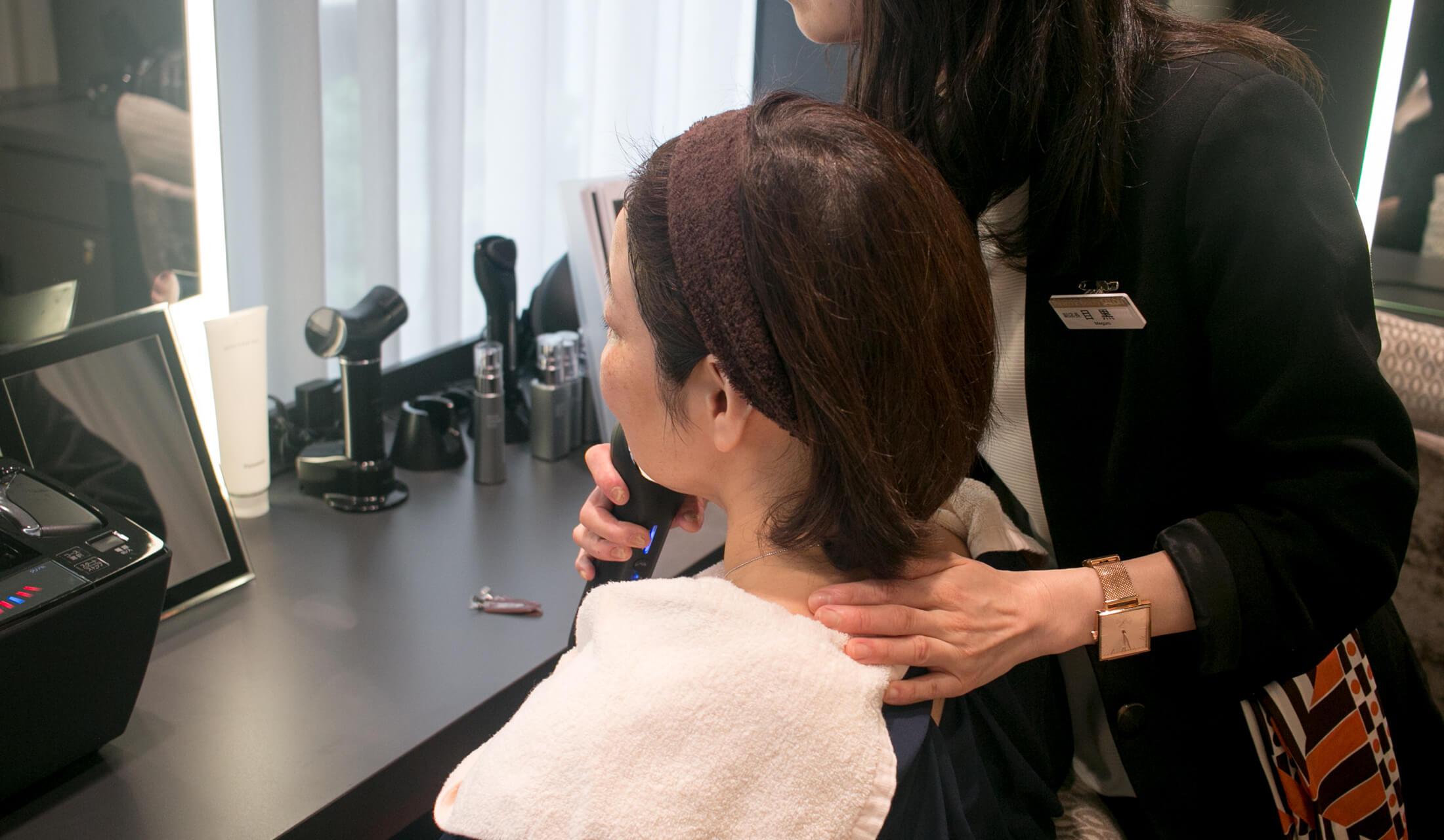 鏡の前に座った女性が、別の女性に美容家電を頬に当ててもらっている