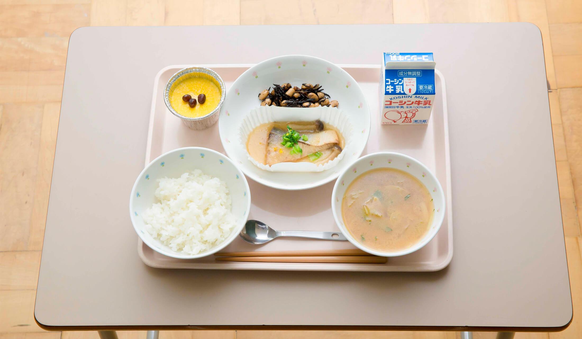 お盆の上に白米、汁物、魚料理、ひじき、牛乳、かぼちゃプリンが並ぶ学校給食