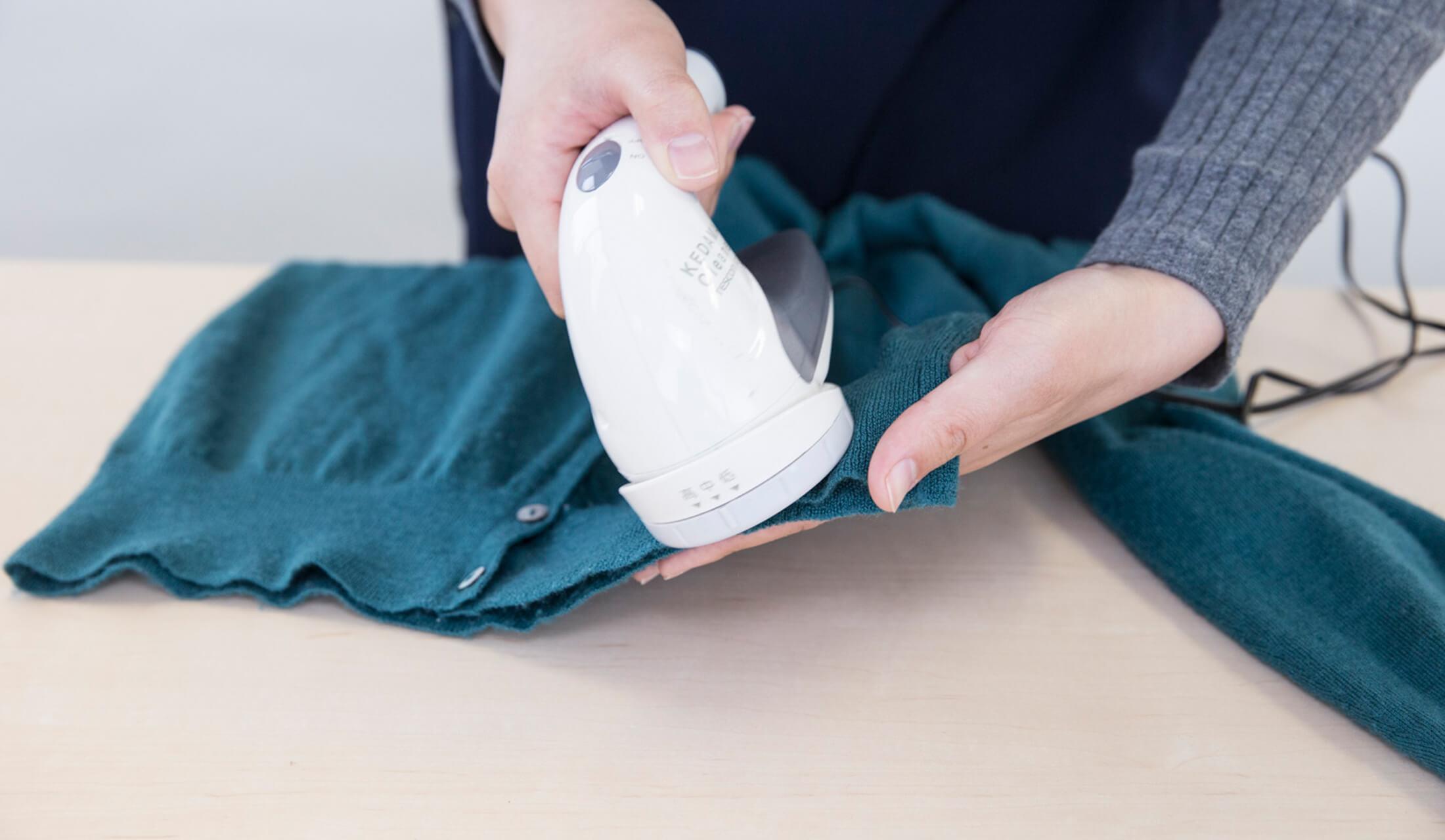毛玉のついたグリーンのニットの裾を女性が手に持ち、白い電動毛玉取り器でケアをしている