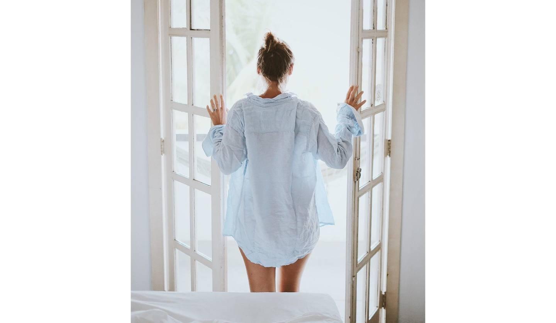 起きて窓を開ける女性