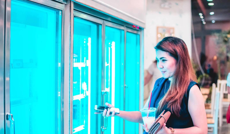 スーパーの冷蔵庫前で商品を選ぶ女性