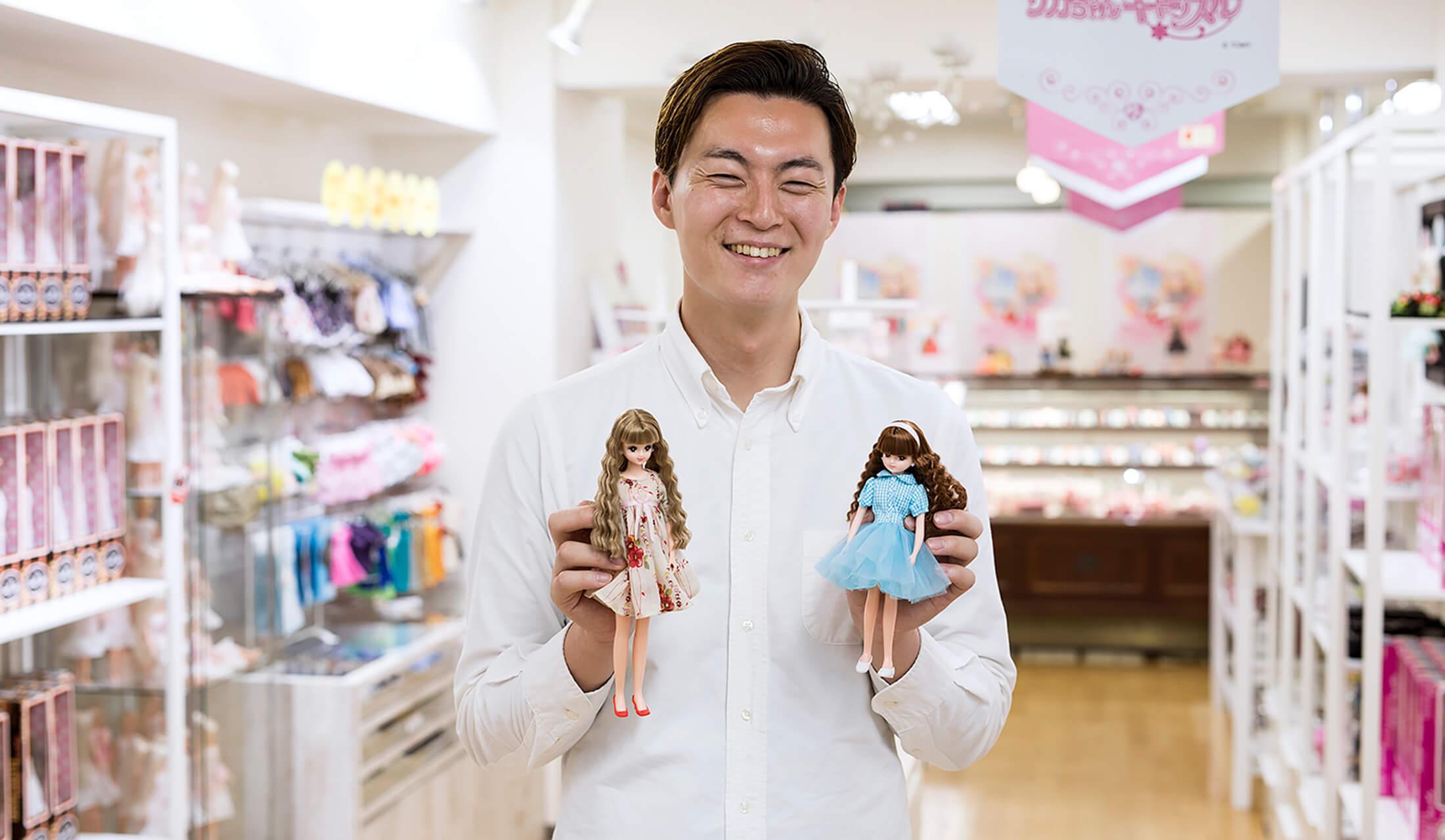 日本橋の「リカちゃんキャッスルのちいさなおみせ」の男性スタッフである広瀬和哉さんがご自身でデザインした服を着せたリカちゃんと、ジェニーを手に持っている