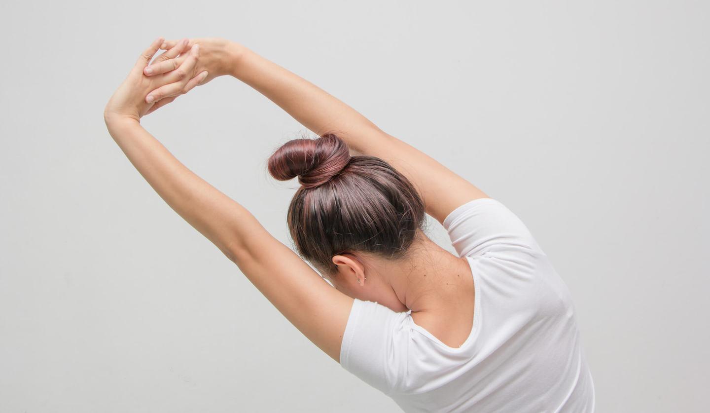 白いTシャツを着た女性が腕を伸ばすストレッチをしている様子
