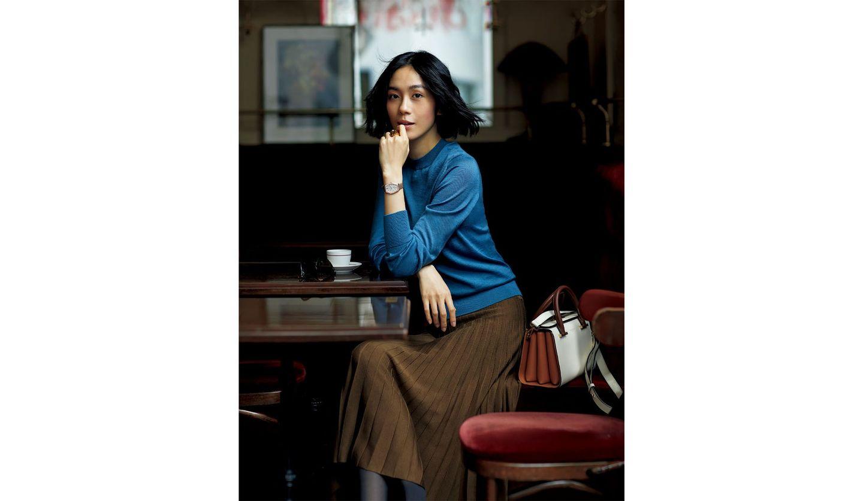 キャメルブラウンにピーコックブルーを合わせたスタイルを纏った女性