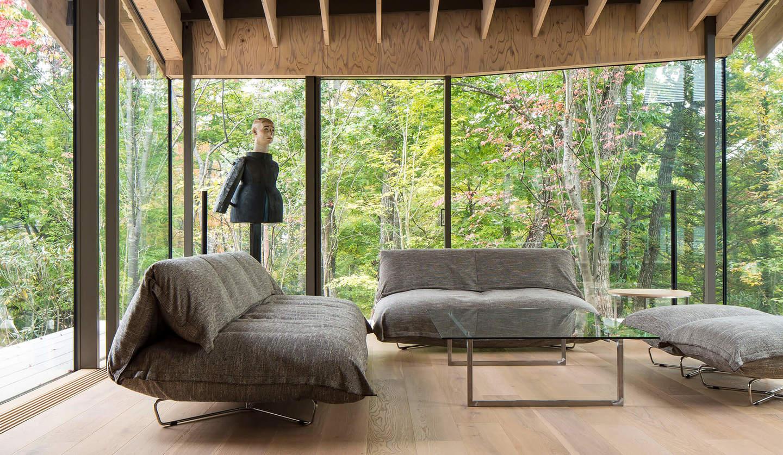 3方が大きな窓に囲まれ外は木々が広がる別荘の部屋に、ローテーブル1つとソファー3つが並ぶ