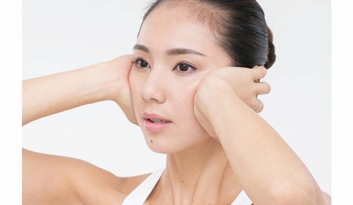 「顔のゆがみ」を矯正するマッサージをしている女性