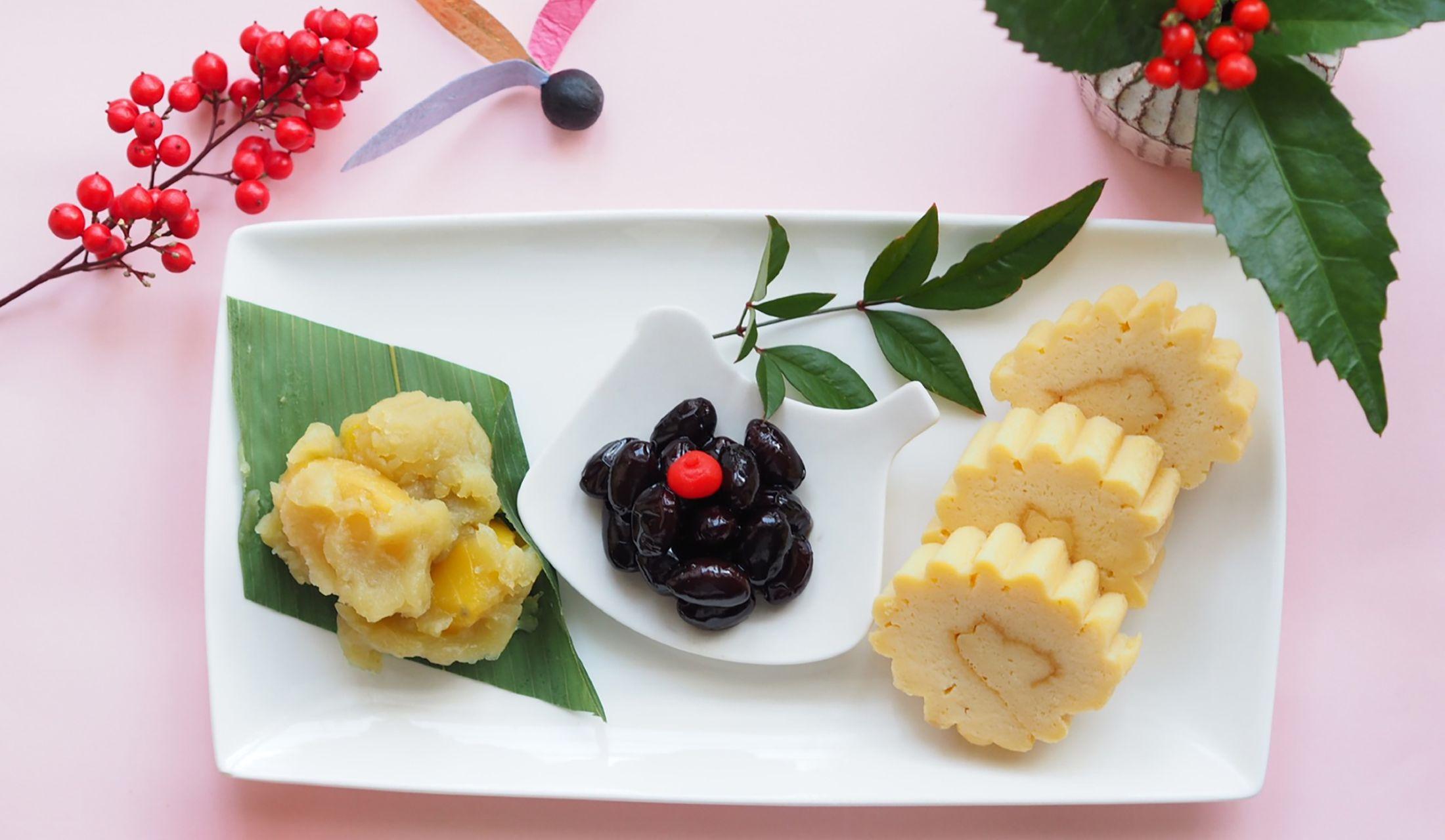 正月料理と南天の実が飾られた食卓