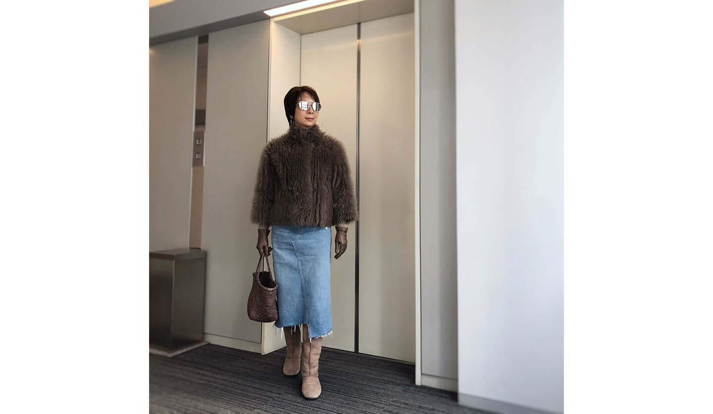 コートとスカートを着てエントランスホールに立つ女性