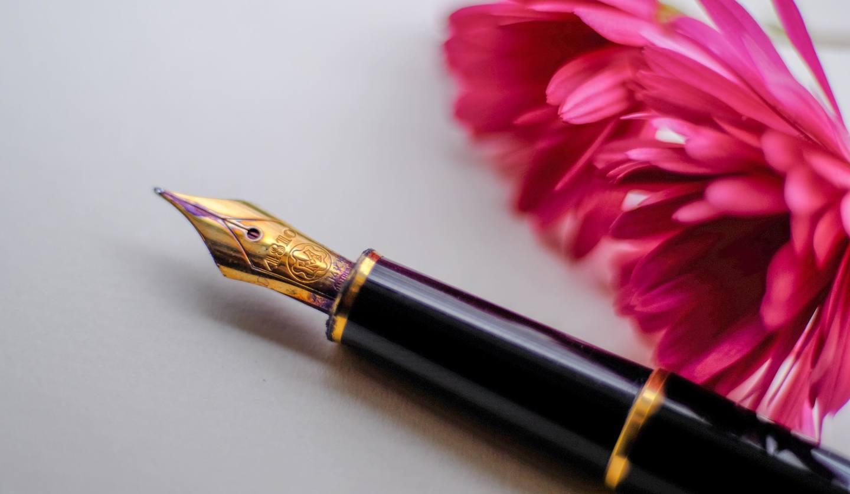 万年筆とピンク色の花