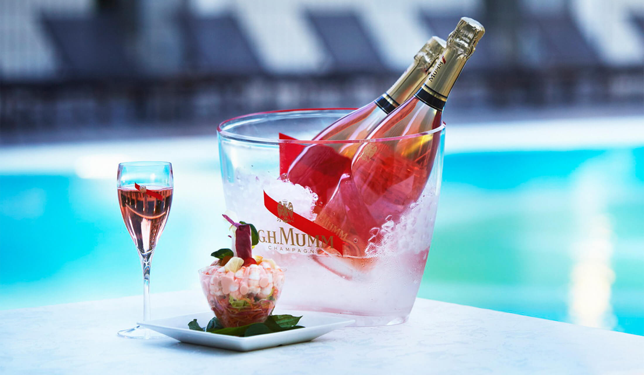 プールサイドに置かれたシャンパンとグラス