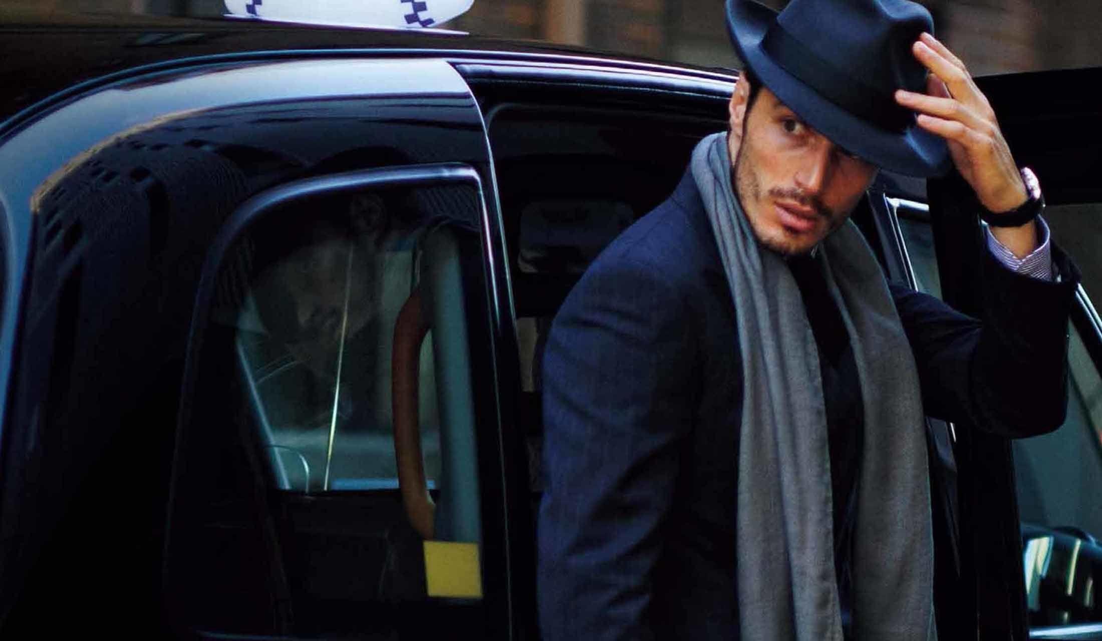ロンドンタクシーから降りてくる帽子をかぶった外国人