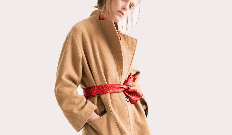 キャメルのコートの上に赤いサッシュベルトを無造作に巻いた金髪の外国人モデル