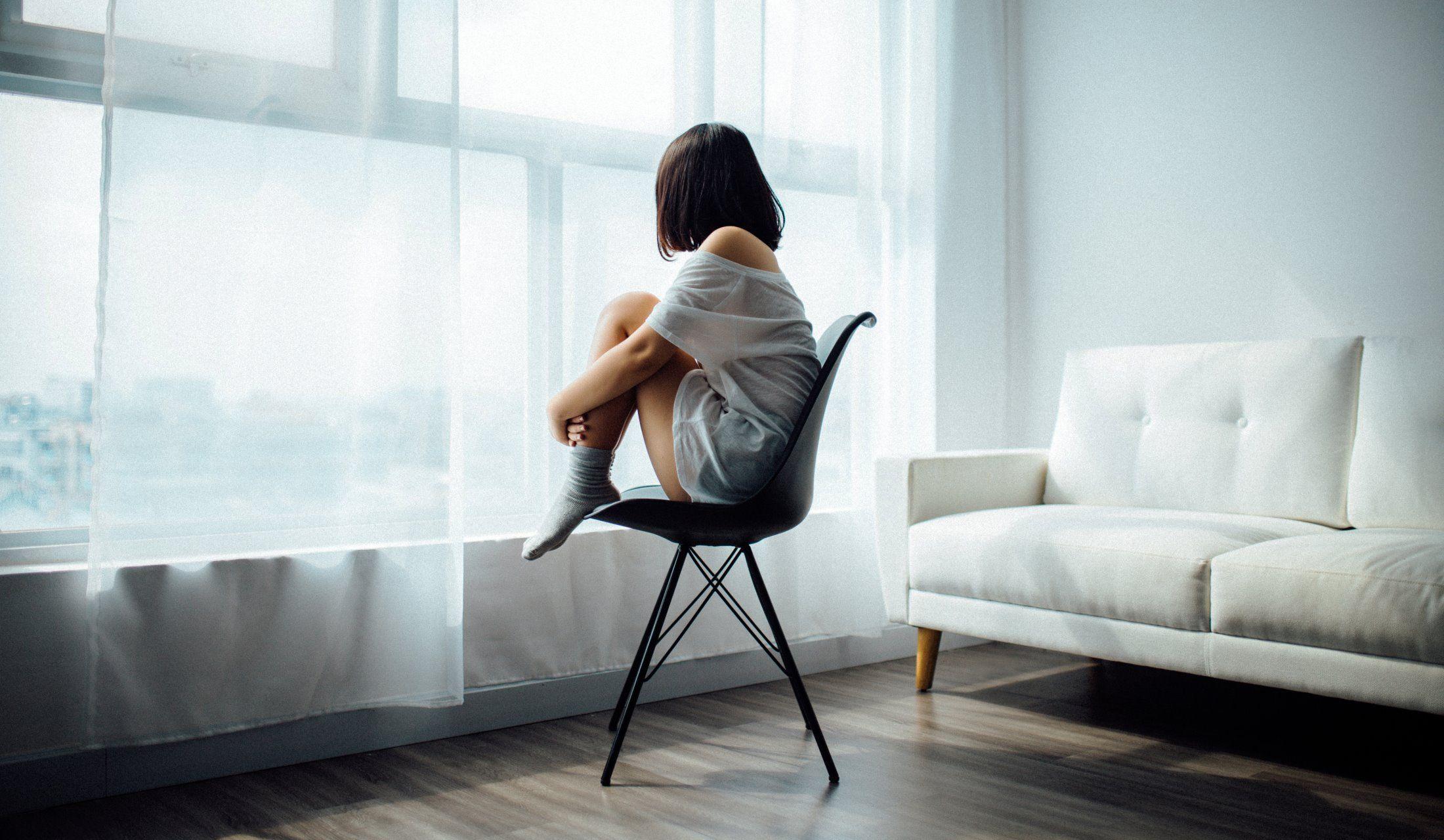 窓際で椅子に体育座りする女性