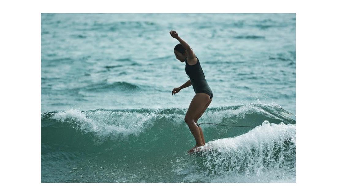 サーフィンで波に乗る女性