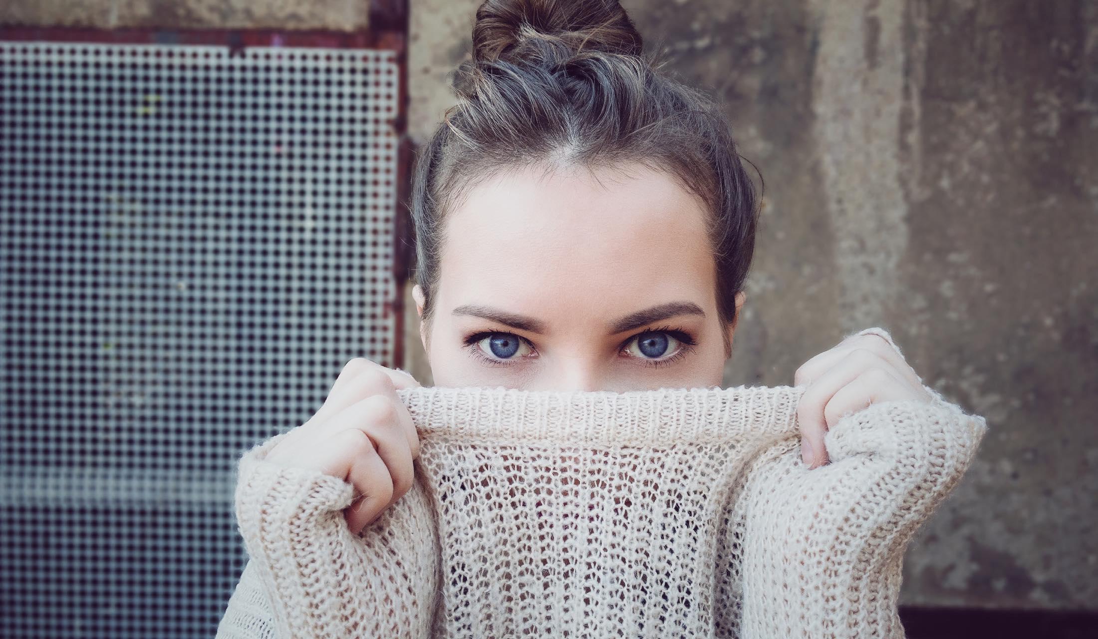 顔の下半分をニットで隠している女性