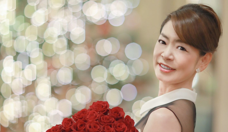 バラの花束を抱えて微笑む安田美佐子さん