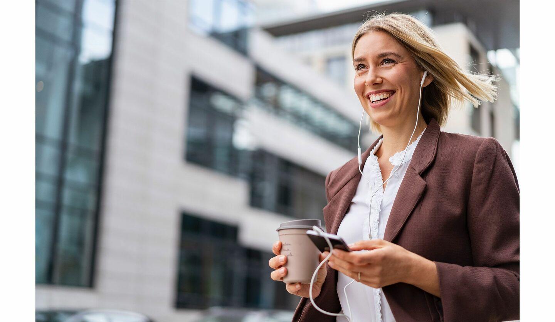 携帯を確認しながら歩くスーツの女性