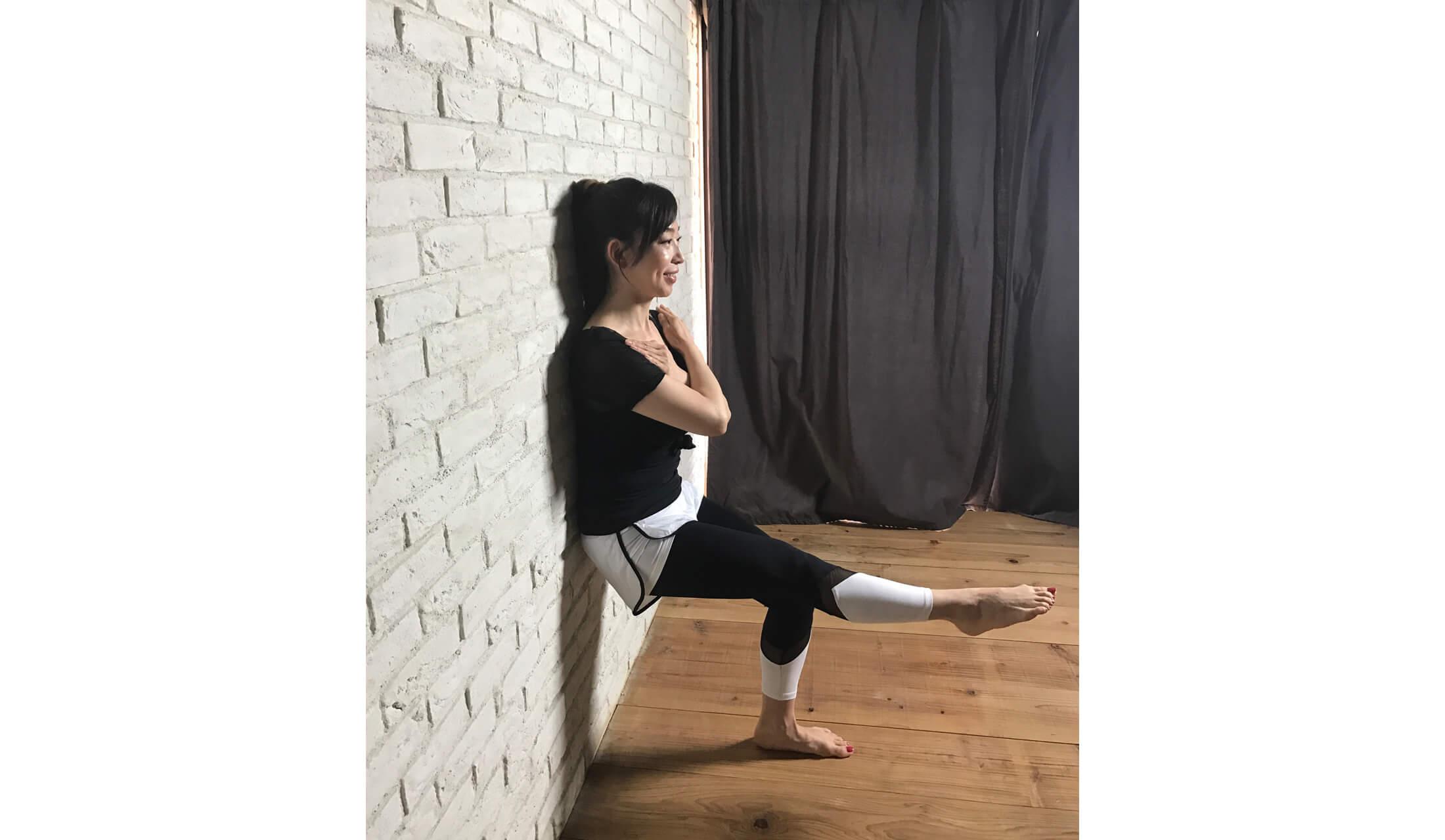 壁に背中をあずけ、空中で座った状態で右脚をまっすぐ伸ばし、壁トレを実践している女性