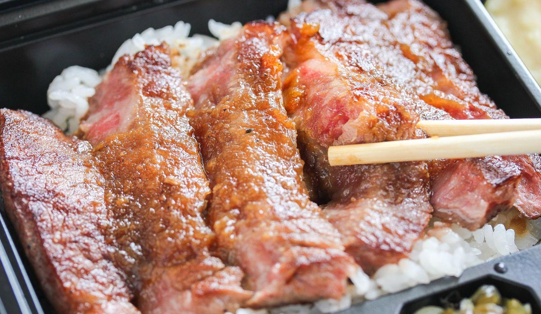 黒い弁当箱に白米とステーキが乗り、箸で肉を一切れつまんでいる