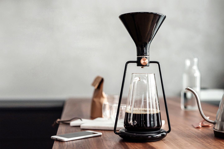 木のテーブルの上に、スロべニアのブランドGOAT STORYのコーヒードリッパーGINAが置かれ、その側にスマートフォンやグラス、コーヒー豆の袋なども置かれている