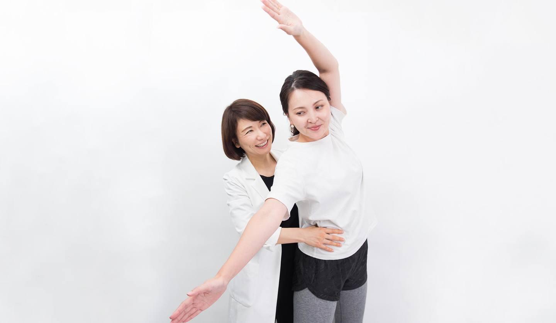 向かい合っている二人の女性 側屈の指導をしている